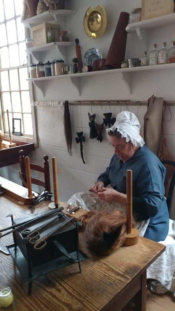 Colonial Williamsburg: a living history re-enactor making a wig