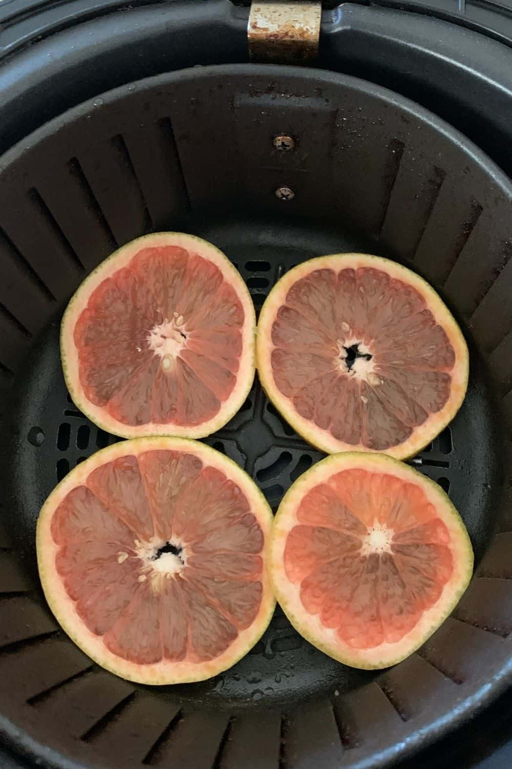 orange slices in the air fryer ready to be dried