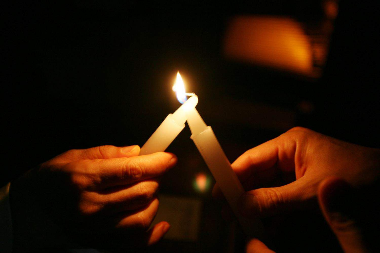 one candle being lit by another candle being held in hands