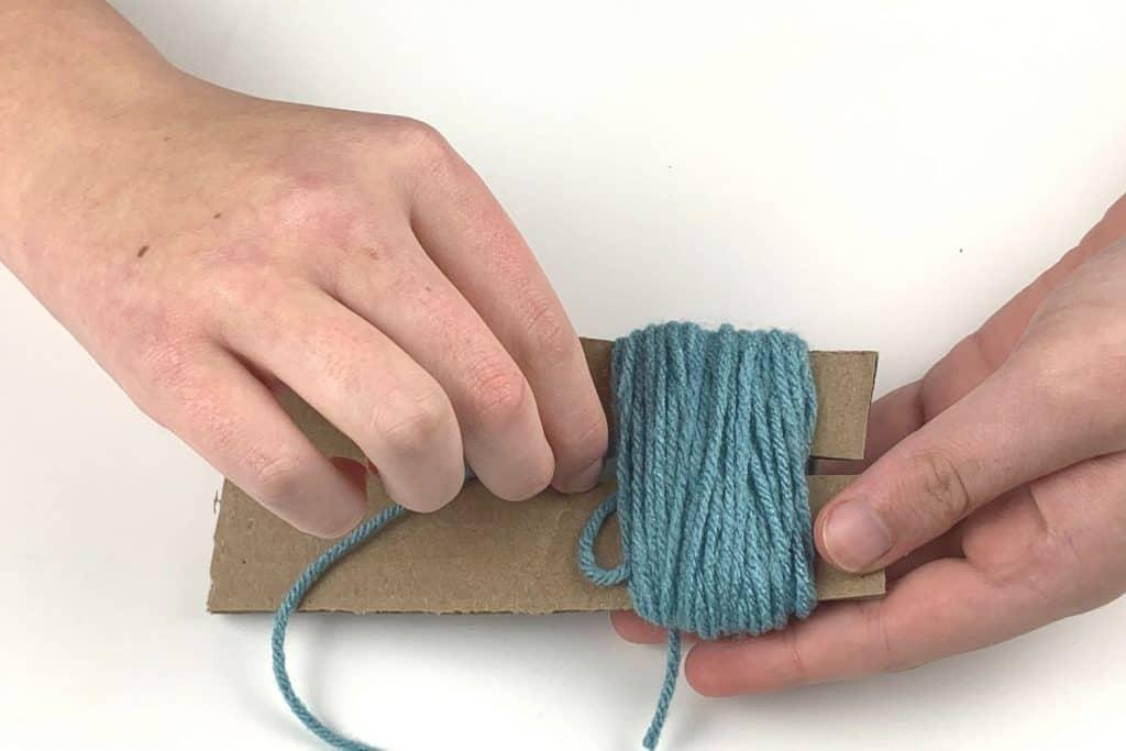 Thread the yarn around the bundle for your pom pom