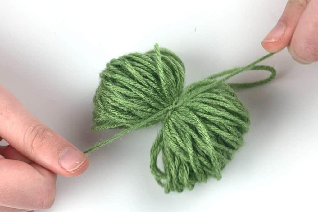 Tighten the yarn around the yarn bundle to create the pom pom