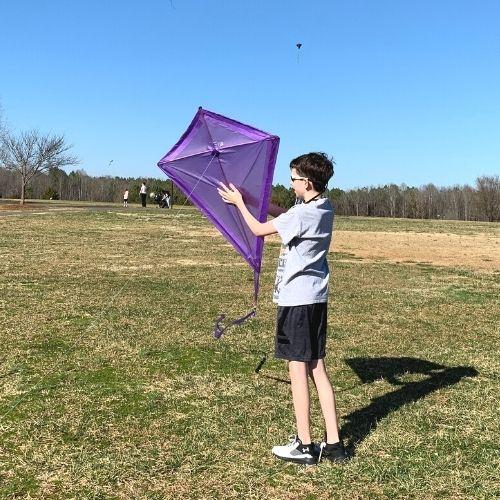 Kid holding a diamond kite