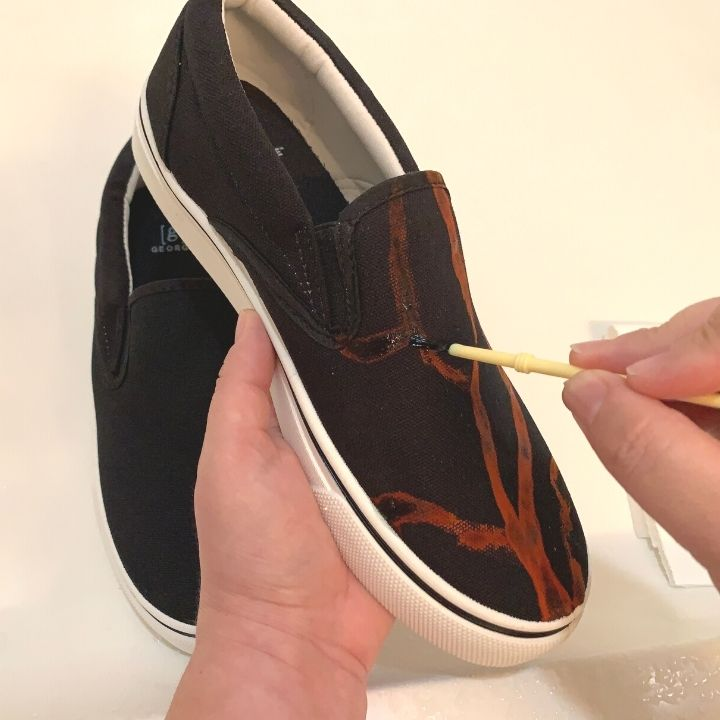 Applying bleach cleaner to the shoes